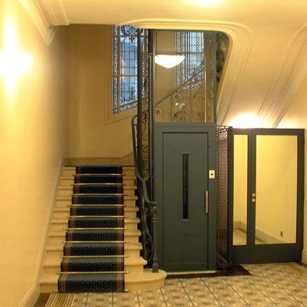 Entrée d'immeuble rénovée, sol carreau de ciment, escalier en pierre, ascenseur métal laqué.