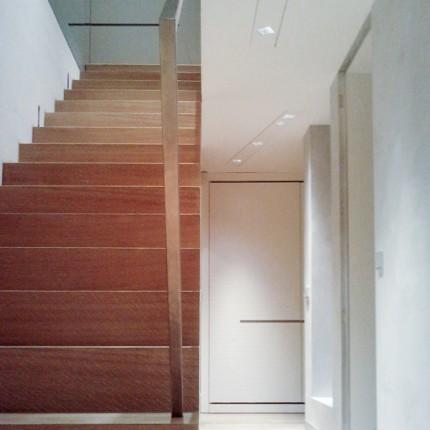 Circulations en chêne verni, murs matière, porte toute hauteur ''L'invisible''