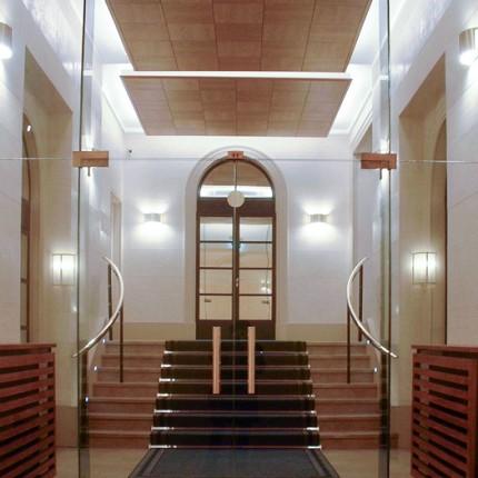 Hall d'accueil de bureaux réhabilité, matériaux pierre, métal & verre. Acoustique bois.
