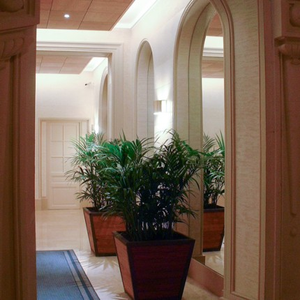 Hall de réception de bureau, sol en pierre, murs d'enduit et double éclairage en hauteur.